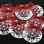 Ten silver card die cut bauble shapes topped with a snowflake, clear gem and red ribbon bow on a black background