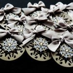 Ten beige card die cut bauble shapes topped with a snowflake, gold gem and beige ribbon bow on a black background