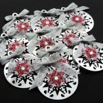 Ten silver card die cut bauble shapes topped with a snowflake, clear gem and silver ribbon bow on a black background