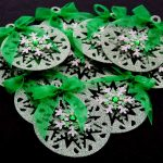 Ten green card die cut bauble shapes topped with a snowflake, green gem and green ribbon bow on a black background