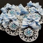 Ten silver card die cut handmade Christmas bauble shapes topped with a snowflake, blue gem and pale blue ribbon bow on a black background