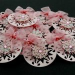 Ten pink card die cut bauble shapes topped with a snowflake, pink gem and pink ribbon bow on a black background