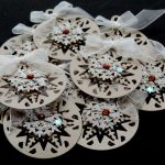 Ten beige card die cut bauble shapes topped with a snowflake, brown gem and white ribbon bow on a black background