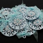 Ten silver card die cut bauble shapes topped with a snowflake, blue gem and pale blue ribbon bow on a black background