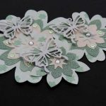 Three handmade 3D three and five layer flowers in green and cream topped with a colour co-ordinated clear gem and smaller flower gems, a cream butterfly on a black background