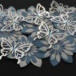 Eight handmade 3D four layer flowers in blue and white topped with a colour co-ordinated blue gem and smaller gems, a silver butterfly with a blue gem centre on a black background