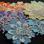 Eight handmade 3D five layer flowers in several different colours topped with colour co-ordinated flower gems and a silver butterfly with multi coloured gem centres on a black background
