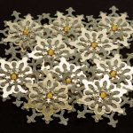 Ten Large handmade die cut snowflakes, two tone gold with a gold gem in the centre on a black background