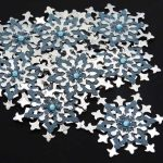 Ten, handmade blue and silver die cut card snowflakes four layers topped with a blue gem on a black background