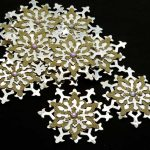 Ten handmade gold and silver large die cut snowflakes four layers with an iridescent gem in the center on a black background