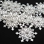 Ten, handmade two tone silver die cut card snowflakes with four layers topped with a silver gem on a black background
