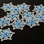 Fifteen handmade white card punched medium sized snowflakes topped with a smaller blue and white card punched snowflakes and a blue gem on a black background