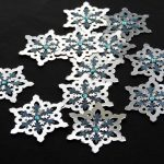 Twelve silvercard punched medium sized snowflakes topped with a smaller blue and silver card punched snowflakes and a blue gem on a black background