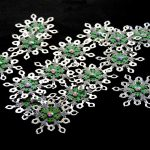 15 handmade silver card punched medium sized snowflakes topped with a smaller green and silver card punched snowflakes and a red gem on a black background