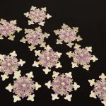 Ten handmade silver card punched medium sized snowflakes topped with a smaller lilac and cream card punched snowflakes and a clear gem on a black background