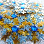 Several blue and gold small card punch cut snowflakes topped off with a blue gem on a silver glitter background.