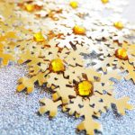 Several handmade gold small card punch cut snowflakes topped off with a gold gem on a silver glitter background.