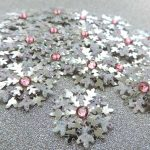 Several handmade silver and glitter small card punch cut snowflakes topped off with a pink gem on a silver glitter background.
