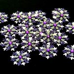 Several handmade silver and purple small card punch cut snowflakes topped off with a purple gem on a black background.