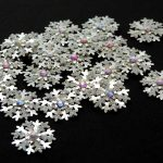 Several silver small card punch cut snowflakes topped off with an iridescent gem on a black background.