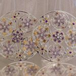 Two handmade silver 4.5 inch round die cut clusters topped with five medium card snowfaked and four small card snowflakes all topped with various gems in purple and golds
