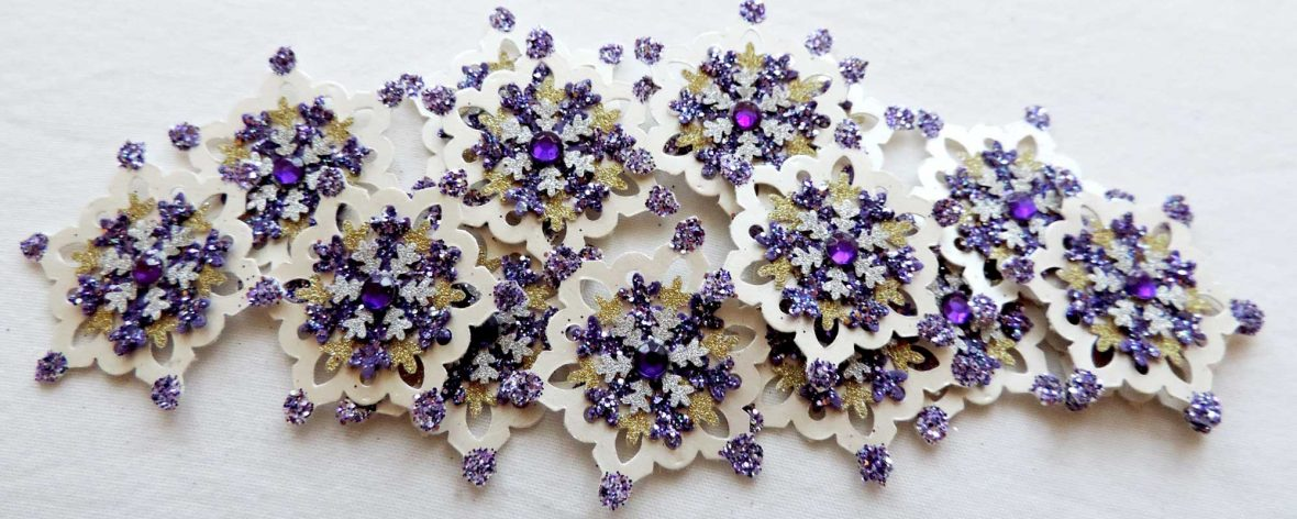 A collection of purple, ivory and gold punch-cut snowflakes with purple centre gemstone.